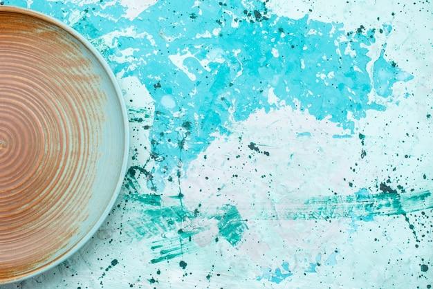 Bovenaanzicht van bruine plaat leeg op lichtblauw, bordvoedsel
