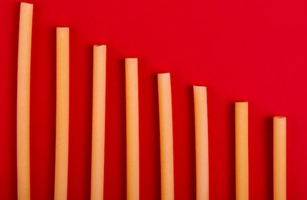 Bovenaanzicht van bucatini pasta op rode ondergrond