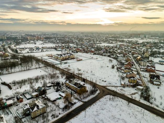 Bovenaanzicht van buitenwijken van de stad of kleine stad mooie huizen op winterochtend op bewolkte hemelachtergrond. luchtfoto drone fotografie concept.