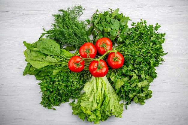 Bovenaanzicht van bundels verse groenten en tomaten met stengel op witte achtergrond