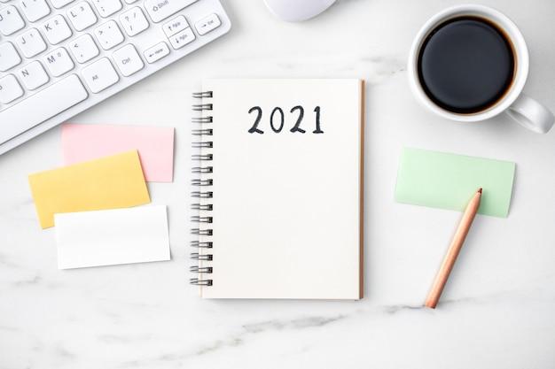 Bovenaanzicht van bureau 2021 doelwerkconcept met toetsenbord, notitieboekje, potlood, bril en koffie