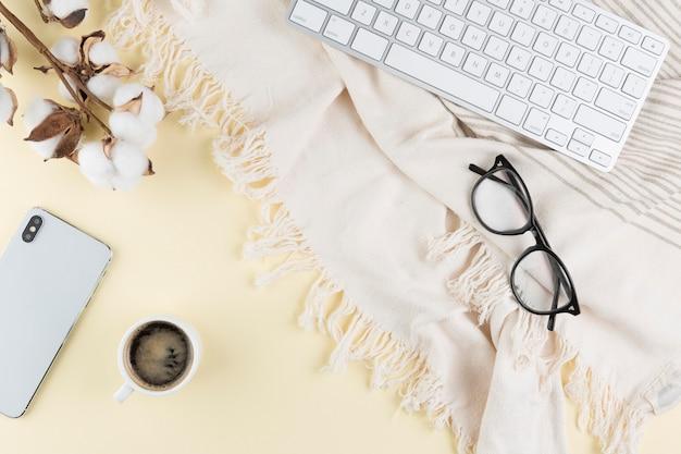 Bovenaanzicht van bureau met bril en smartphone