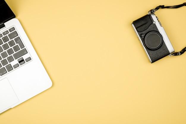 Bovenaanzicht van bureau met camera en laptop