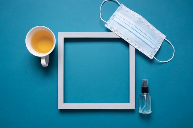 Bovenaanzicht van bureau met frame en medisch masker naast thee