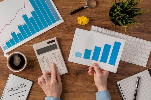 Bovenaanzicht van bureau met groeigrafiek en handen met behulp van kleine rekenmachine