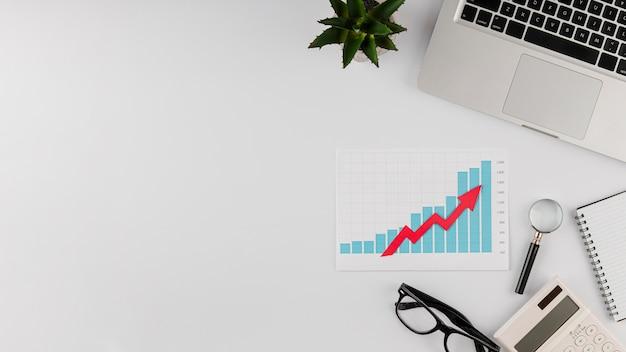 Bovenaanzicht van bureau met groeigrafiek en kopie ruimte