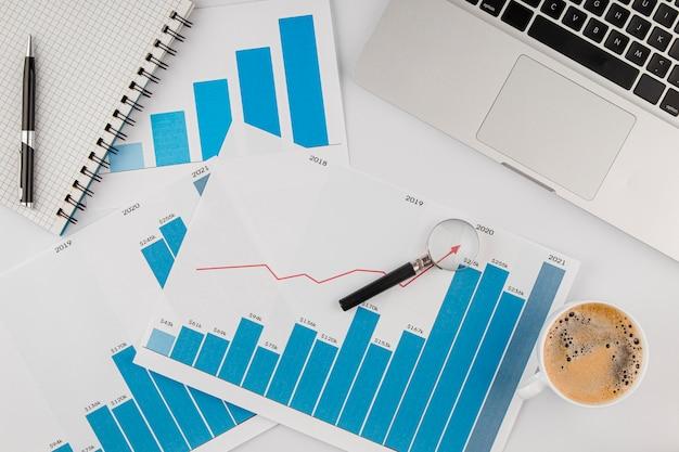 Bovenaanzicht van bureau met groeigrafiek en laptop