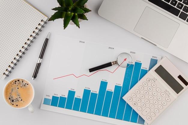 Bovenaanzicht van bureau met groeigrafiek en rekenmachine