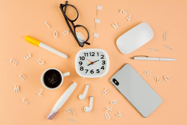 Bovenaanzicht van bureau met klok en koffie