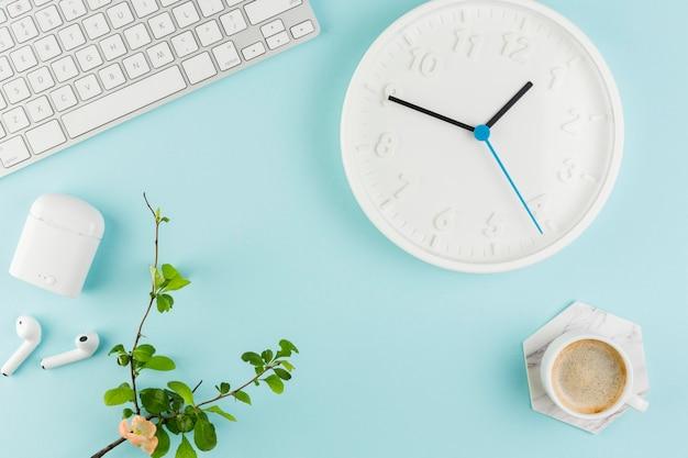 Bovenaanzicht van bureau met klok en plant