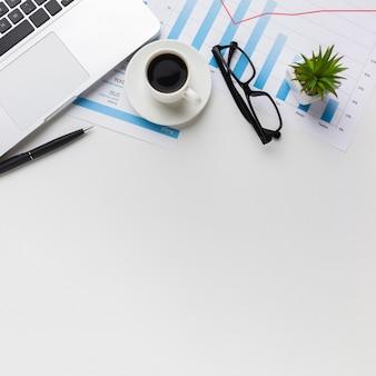 Bovenaanzicht van bureau met koffie en laptop