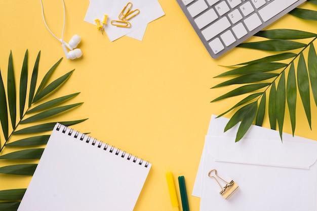 Bovenaanzicht van bureau met laptop en bladeren