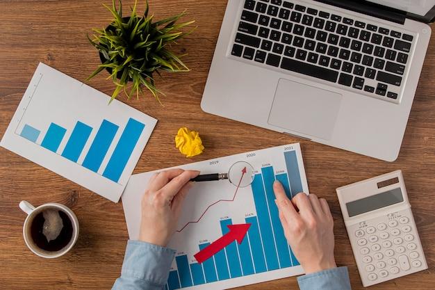 Bovenaanzicht van bureau met laptop en groeigrafiek door handen geanalyseerd
