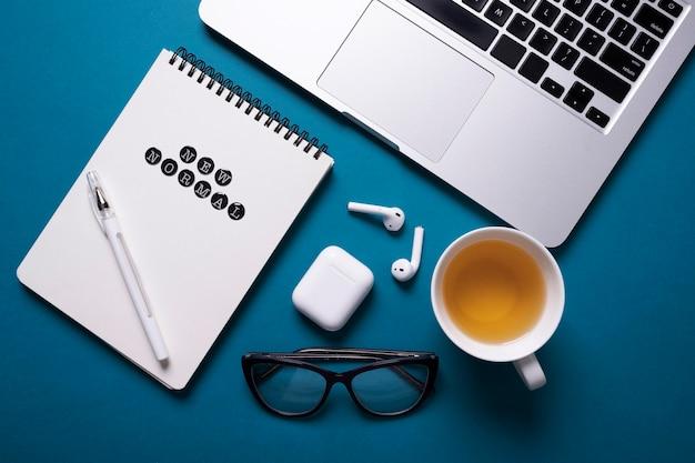 Bovenaanzicht van bureau met laptop en notitieboekje naast thee