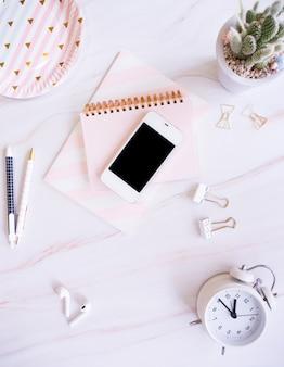 Bovenaanzicht van bureau met smartphone, wekker en kantoorbenodigdheden