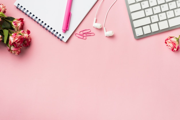 Bovenaanzicht van bureau met toetsenbord en boeket rozen