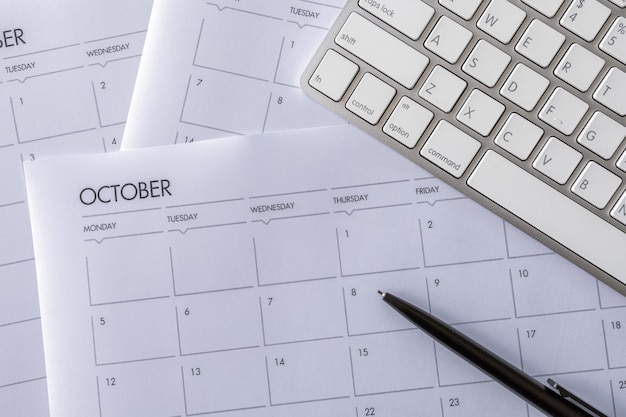 Bovenaanzicht van bureau met toetsenbord en werkschema op witte tafel