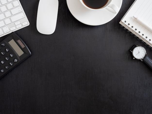 Bovenaanzicht van bureau tafel met laptop, plastic plant, rekenmachine en toetsenbord op zwarte achtergrond, grafisch ontwerper, creatief ontwerper concept.