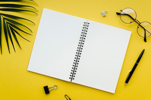 Bovenaanzicht van bureaublad met bril en laptop