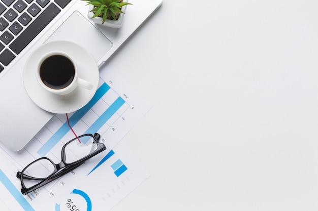 Bovenaanzicht van bureaublad met laptop en glazen