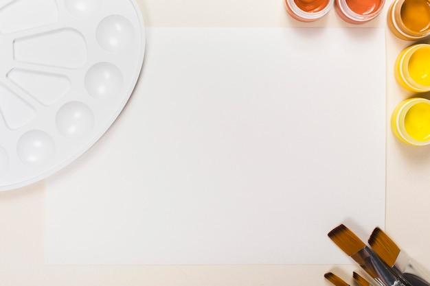Bovenaanzicht van bureauconcept met verf en exemplaarruimte