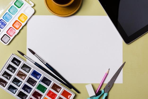 Bovenaanzicht van bureauconcept met verf en exemplaarruimte Gratis Foto