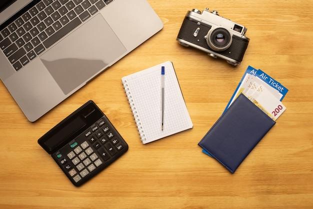 Bovenaanzicht van bureautafel voor kantoorfotografie met laptop, notebook, camera, rekenmachine en paspoort met vliegticket.