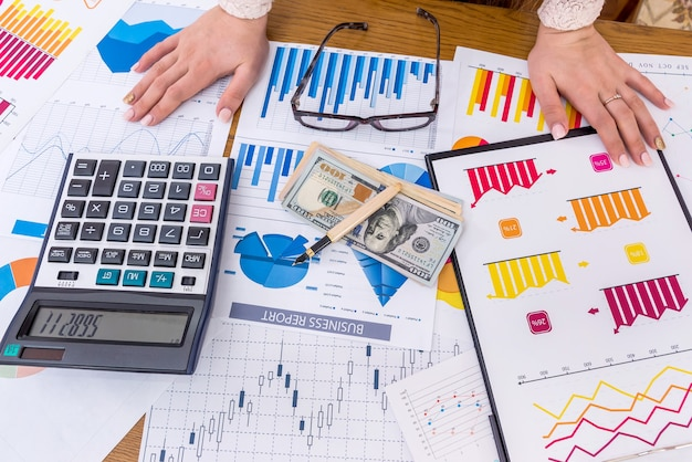 Bovenaanzicht van business analist werkplek met vrouwelijke handen