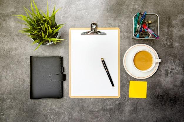 Bovenaanzicht van business desk met ingegoten plant, klembord, notebook, koffie, notities papier en zakelijke accessoires