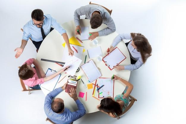 Bovenaanzicht van business team op werkruimte muur