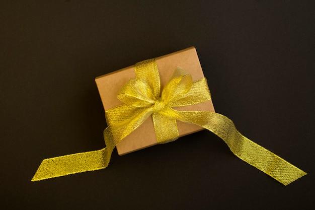 Bovenaanzicht van cadeau met gouden strik op het zwarte oppervlak