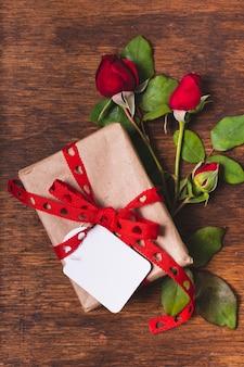 Bovenaanzicht van cadeau met roos boeket en tag