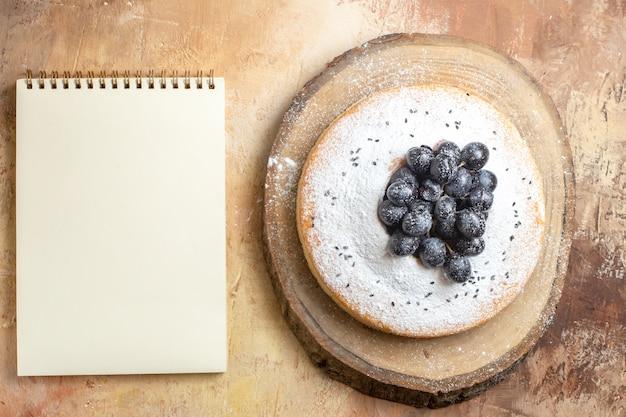 Bovenaanzicht van cake een cake met zwarte druiven op het witte notitieboekje van de snijplank
