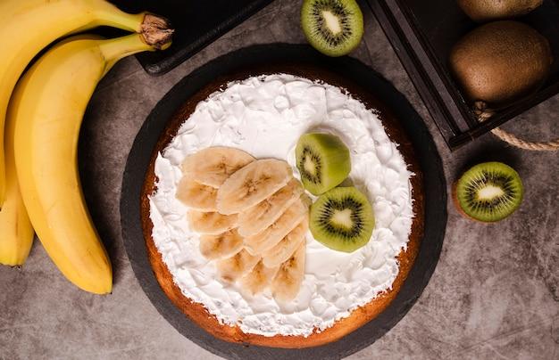 Bovenaanzicht van cake met plakjes banaan en kiwi
