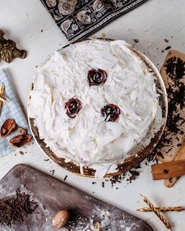 Bovenaanzicht van cake versierd met witte chocoladestukjes op tafel