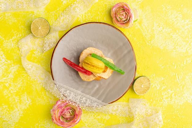 Bovenaanzicht van cakeplak met macaron en marmelade binnen plaat op geel oppervlak
