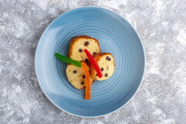 Bovenaanzicht van cakeplakken in blauw bord met choco chips en marmelade op rustieke grijze ondergrond