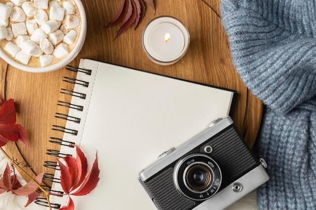 Bovenaanzicht van camera en notebook met kop warme chocolademelk met marshmallows
