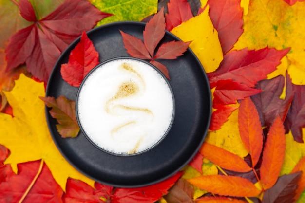 Bovenaanzicht van cappuccino koffiekopje op herfst achtergrond met gekleurde bladeren