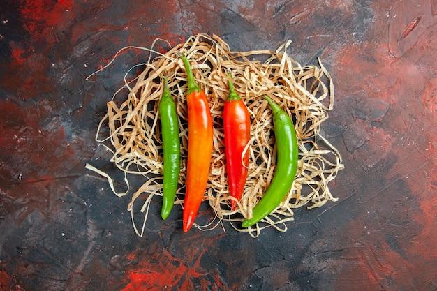 Bovenaanzicht van cayennepeper in verschillende kleuren en maten op tafel met gemengde kleuren