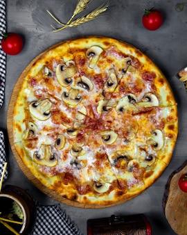 Bovenaanzicht van champignonpizza met tomatensaus en kaas