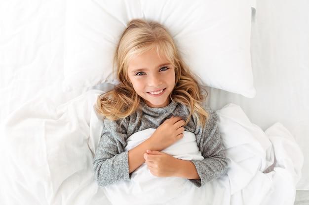 Bovenaanzicht van charmante blonde meisje glimlachend en liggend in bed