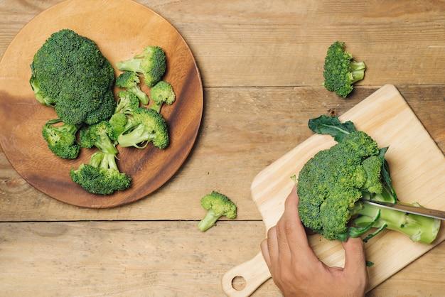 Bovenaanzicht van chef-kok die broccoli met de hand snijdt om te koken