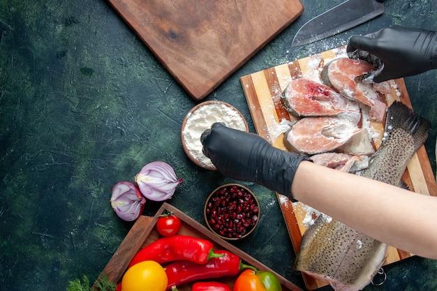 Bovenaanzicht van chef-kok die rauwe visplakken bedekt met meel, verse groenten op houten bord, meelkommes op keukentafel