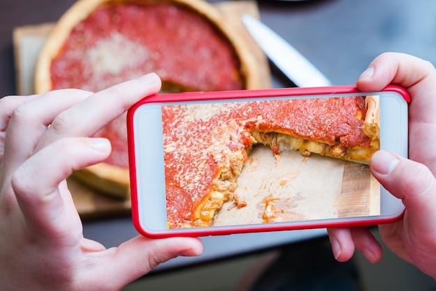 Bovenaanzicht van chicago pizza. vrouw handen nemen foto met slimme telefoon.