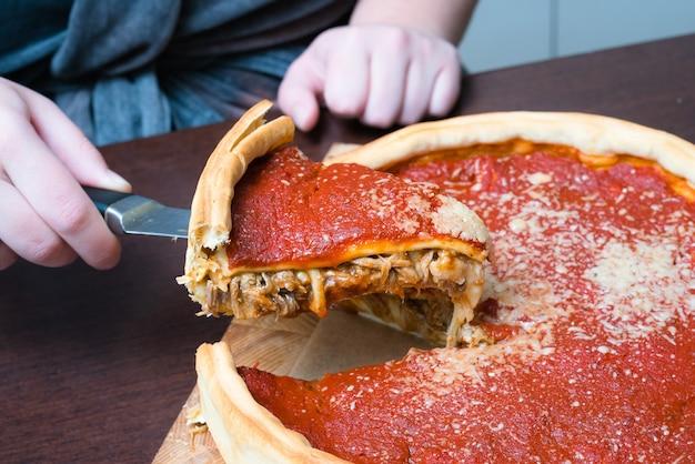 Bovenaanzicht van chicago pizza - vrouw handen snijden chicago stijl diepe schotel italiaanse kaas pizza.