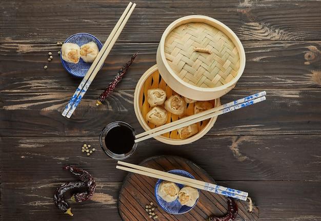 Bovenaanzicht van chinees vlees knoedel gestoomde schotel in bamboe stoomboot doos met eetstokjes