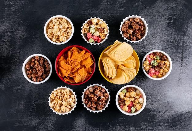 Bovenaanzicht van chips en popcorn in kommen op zwarte horizontaal