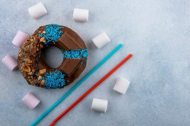 Bovenaanzicht van chocolade donut met marshmallows en blauw met rode rietjes op een grijze ondergrond