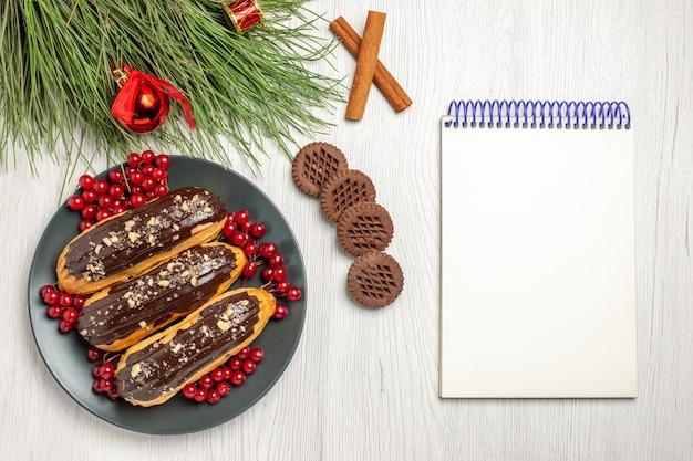 Bovenaanzicht van chocolade-eclairs en aalbessen op de grijze plaat koekjes gekruist kaneel en dennenboom bladeren met kerst speelgoed en een notitieblok op de witte houten tafel